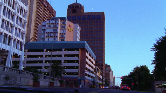 driving on city street in memphis, tennessee. comfort inn, parking garage, skyscrapers office buildings on left. motels. - inn stock videos and b-roll footage