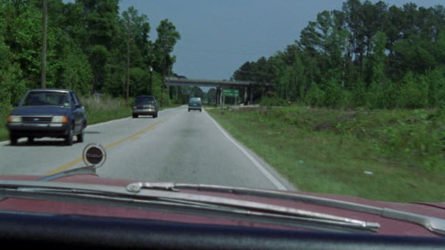 """DRIVING POV. DRIVES ON TWO LANE HIGHWAY PAST ROAD SIGN READING """"MEMPHIS 114 / LITTLE ROCK 308."""" DASHBOARD, HOOD AND HOOD ORNAMENT OF RED 1966 BUICK WILDCAT CAR."""