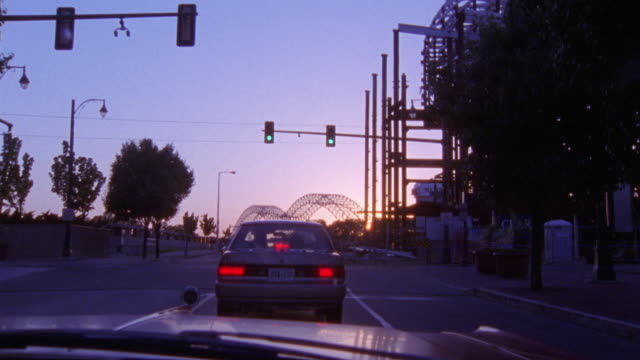 "DRIVING ON CITY STREET IN MEMPHIS TOWARDS MEMPHIS ""M"" BRIDGE. DRIVES THROUGH INTERSECTION."