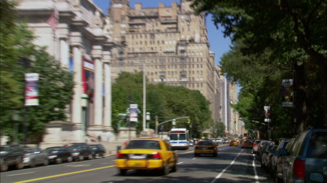 medium angle of new york city street. see cars driving both ways on street. see museum of natural history building in foreground. camera zooms in and pulls back to museum various times. - upper west side manhattan stock videos and b-roll footage