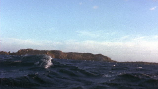 wide angle of choppy waves of ocean or sea waters. see rocky island in background. camera mounted on boat and image rocks from side to side. - sardinien stock-videos und b-roll-filmmaterial
