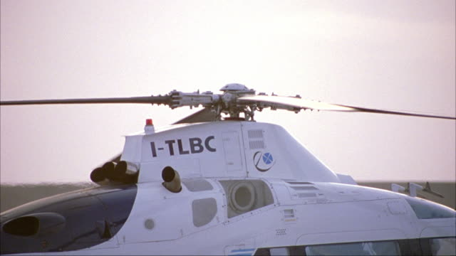medium angle of helicopter preparing to take off. helicopter blades and rotor begin to spin. camera pans to various parts of helicopter. possibly private helicopter on helipad at airport or roof of building. neg cut. - anno 2002 video stock e b–roll