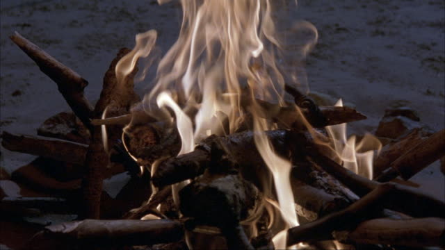 close angle of campfire burning on beach. pov zooms in to flames. see smoke and logs. sand. - anno 2002 video stock e b–roll