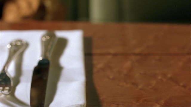"vídeos y material grabado en eventos de stock de close angle of a woman's hand lighting a cigarette lighter at an elegant dinner table. see silverware on napkin, an unfiltered cigarette in an ashtray, and a ""forbes"" magazine. - modales de mesa"
