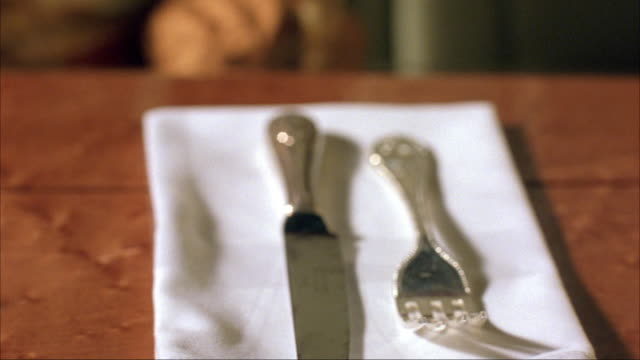 """vídeos y material grabado en eventos de stock de close angle of a woman's hand lighting a cigarette lighter at an elegant dinner table. hand has large white ring. see silverware on napkin, an unfiltered cigarette in an ashtray, and a """"forbes"""" magazine. - modales de mesa"""