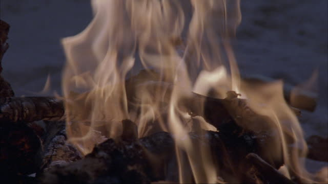 close angle of campfire burning on beach. see smoke and logs. sand. - anno 2002 video stock e b–roll
