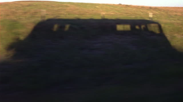 process plate straight left side of country highway or freeway. fields or countryside landscape on both sides of road. see power lines. small ponds in the pastures or plains beyond shadow of rv. - camper van stock videos and b-roll footage