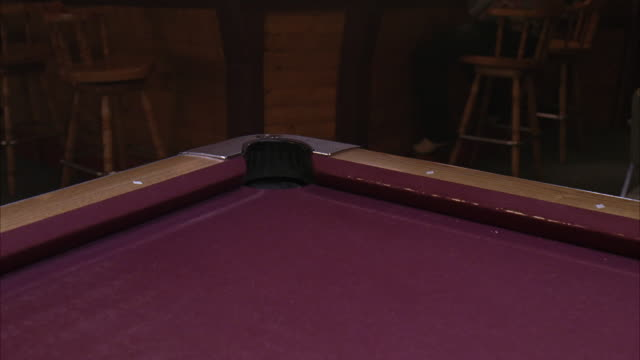 medium angle of purple pool table in bar or tavern or pool hall. cue ball and blue ball roll into corner pocket. billiards. - cue ball stock videos & royalty-free footage