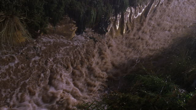 HIGH ANGLE DOWN OF HEAVY RAIN RUNOFF WHICH FORMS FLOOD WATER RIVER IN MOUNTAINOUS, ROCKY CHUTE.