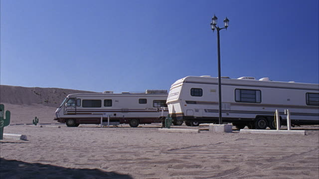 wide angle of desert parking lot. could be for campground or national park. rvs, campers parked near lamp posts. could be trailer park. - trailer stock videos & royalty-free footage