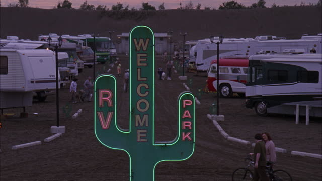 """stockvideo's en b-roll-footage met wide angle of an rv park. large cactus shaped sign reads: """"welcome/rv park.""""  rvs lined up on either side of dirt pathway or road. men, women, and children walk up and down road. people. likely southwest. matching. - opeenvolgende serie"""