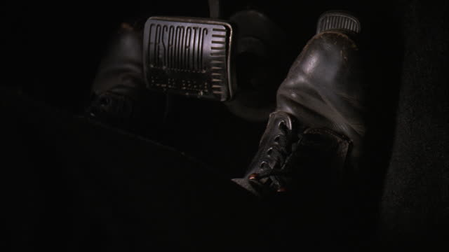 CLOSE ANGLE OF FOOT IN LEATHER SHOE PRESSING PEDALS IN VINTAGE  CAR.