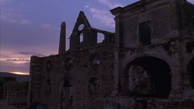 vidéos et rushes de wide angle of brick building with arches and round windows, smoke stacks. could be church or temple ruins. sunset seen over mountain in background. low clouds. - vestige antique