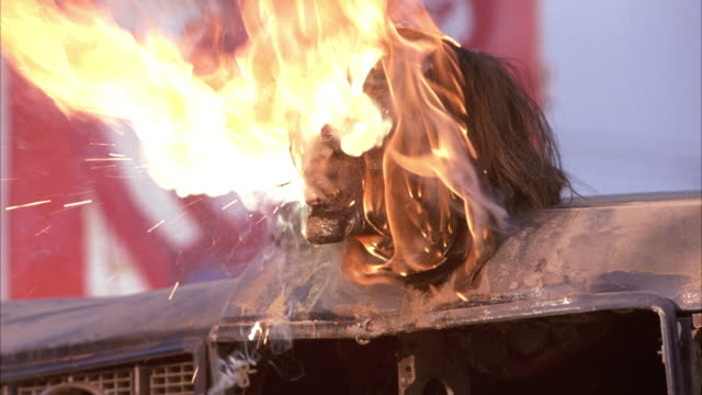 vídeos de stock, filmes e b-roll de close angle of dead man's decomposing head mounted on the hood of a parked car. head burst into flames, flesh melts away revealing skull, which crumbles. fires. deaths, dead. gore. - a. gore