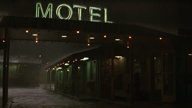 "medium angle of entrance to motel. see neon sign that reads ""motel"" on top of porte-cochere with dim lights. see doors to rooms of motel in the background. - motel stock videos and b-roll footage"