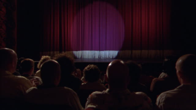 wide angle of theater stage from audience pov. see people sitting in foreground cheering and clapping. see spotlight on red stage curtain. four bald men sit in front of camera. - in front of stock videos and b-roll footage