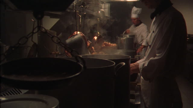 medium angle of kitchen interior. see two men chefs stand in front of steaming pots and kitchen grill. one chef wears tall white head chef hat. pots and pans hang on rack over counter. see box of onions. could be restaurant kitchen. - chef's hat stock videos & royalty-free footage