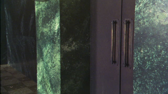 close angle of large double metal doors. see green marble pattern on walls. doors open. - anno 1925 video stock e b–roll