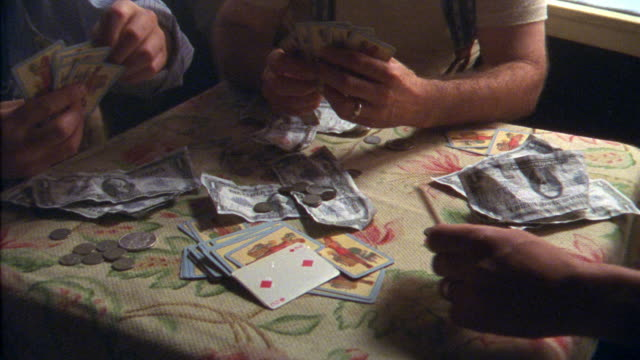 close angle of three men playing poker game or gambling. see hands holding playing cards. pile of money and coins and cards in middle of small table. - poker card game stock videos and b-roll footage