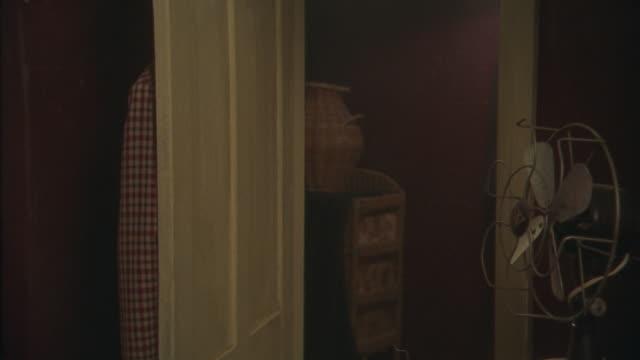 medium angle of bedroom door. see fan on right side. bedroom door is open with clothes hanging on it. see baskets on other side of doorway. - bedroom doorway stock videos & royalty-free footage