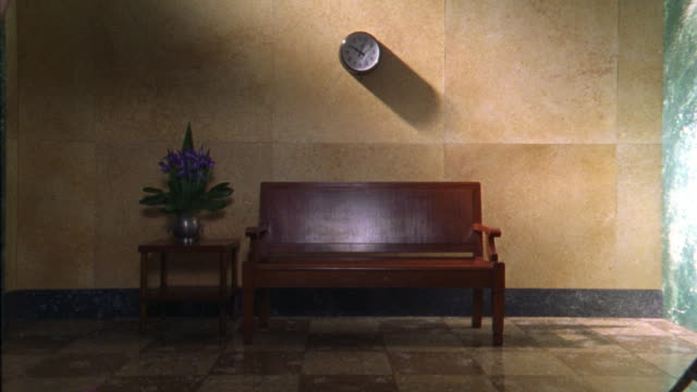 medium angle of wooden bench beneath wall clock. small wooden table with potted plant next to bench. marble tile floor and wall. could be waiting room. - marble wall stock videos and b-roll footage