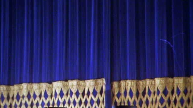 close angle of heavy blue theater curtain with gold trim fall. could be concert hall. - anno 1925 video stock e b–roll