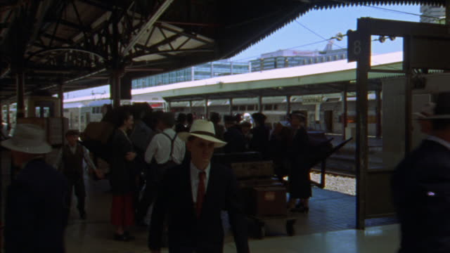 vidéos et rushes de wide angle of crowd in union station platform. business people, travelers, tourists, man with luggage and woman with baby carriage pass in front of camera. - union station los angeles