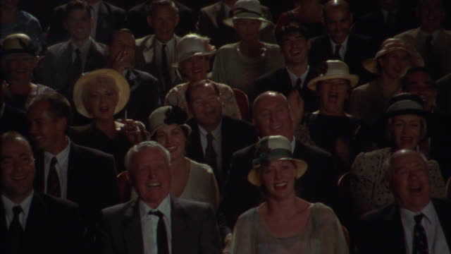 vídeos de stock, filmes e b-roll de medium angle of men and women in theater audience or crowd. see people laughing and watching intently. many men in suits and women in hats. see crowd clapping then giving standing ovation. neg cut. - rindo