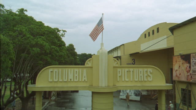 "wide angle of entrance to ""columbia pictures"" movie studio lot. american flag waves in center of shot. camera cranes down to reveal vintage cars driving and actors or workers in background. an actor passes right to left. could be 1930s era. - 1930 stock-videos und b-roll-filmmaterial"