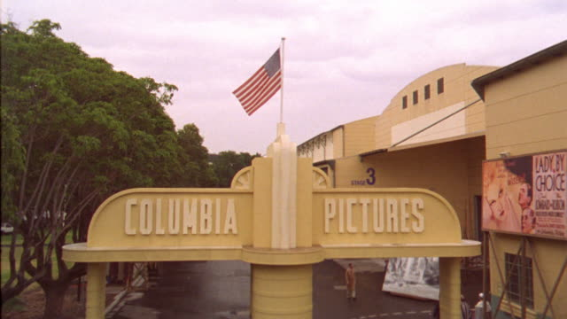 "wide angle of entrance to ""columbia pictures"" movie studio lot. american flag waves in center of shot. camera cranes down to reveal vintage cars driving through frame and actors or workers in background. - columbia center stock videos & royalty-free footage"