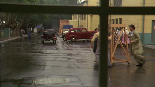 WIDE ANGLE THROUGH WINDOW OF ACTIVITY IN MOVIE STUDIO LOT. WOMEN PASS RIGHT TO LEFT, MEN PUSH WOODEN CART RIGHT TO LEFT, WORKERS CARRY WOODEN PROP, AND A WOMAN WITH FUR COAT WALKS AT FRAME LEFT.