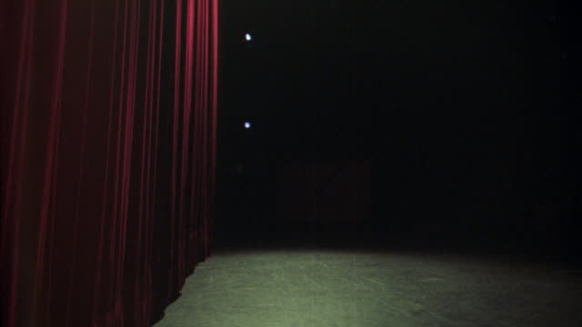 medium angle of theater stage and red curtain. see dark reflective floor in front of red curtain on left. light shines down from top on curtain and stage floor. - 1925年点の映像素材/bロール
