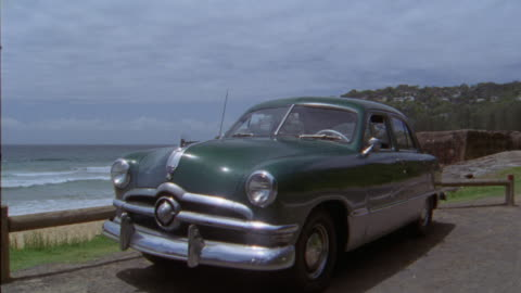 vidéos et rushes de wide angle of 1949 ford sedan. waves come into shoreline. houses on hill in background. sand. water. shores. ocean. pacific coast. classic cars. - 1949