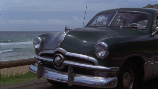 wide angle of 1949 ford sedan. waves come into shoreline. houses on hill in background. sand. water. shores. ocean. pacific coast. classic cars. - 1949 bildbanksvideor och videomaterial från bakom kulisserna