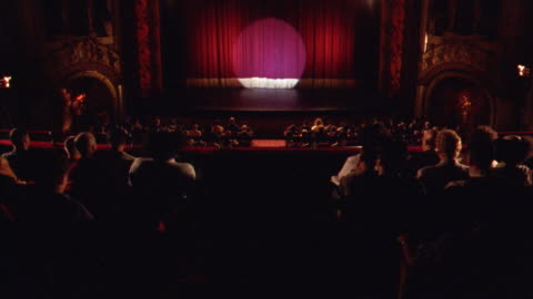 wide angle of theater stage and curtain seen from back of theater. audience is seated and applauds as two latecomers find their seats. - theatre building stock videos & royalty-free footage