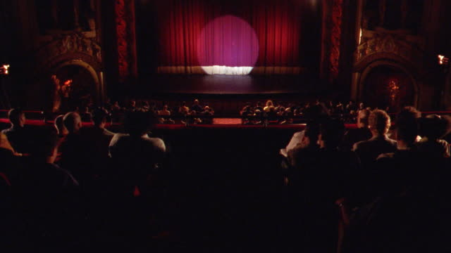 WIDE ANGLE OF THEATER STAGE AND CURTAIN SEEN FROM BACK OF THEATER. AUDIENCE IS SEATED AND APPLAUDS AS TWO LATECOMERS FIND THEIR SEATS.