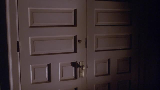 MEDIUM ANGLE OF LEFT DOOR OPENING FROM OUTSIDE IN WHITE FRENCH DOOR FRONT DOORS OR DOORWAY OR ENTRANCE. SEE DOOR SWING OPEN. SEE BRASS DOOR KNOB, KEYHOLE, AND HINGES.