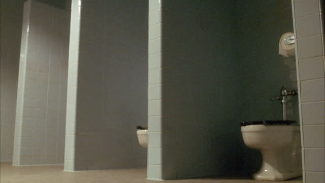 medium angle of public restroom or bathroom stalls. see sky or light blue colored wall tiles, white porcelain toilets with black toilet seats, and no doors on stalls. - public restroom stock videos and b-roll footage