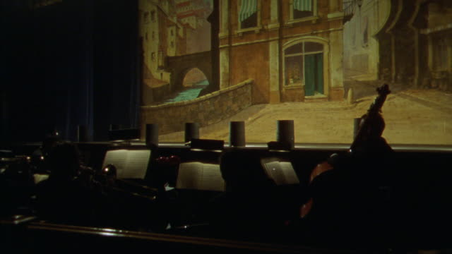 wide angle of orchestra pit and musicians in front of theater stage. see painted backdrop of european town, with heavy blue theater curtain to left of frame. - anno 1925 video stock e b–roll