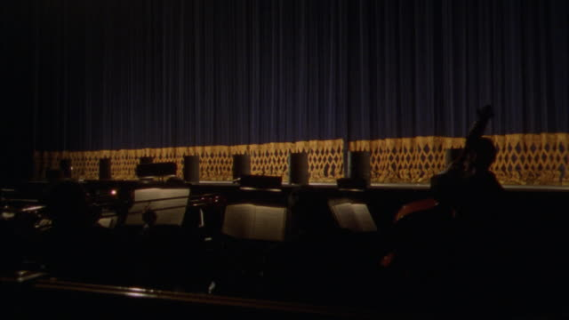 WIDE ANGLE OF ORCHESTRA PIT AND MUSICIANS IN FRONT OF THEATER STAGE.  HEAVY BLUE THEATER CURTAIN WITH GOLD TRIM FALLS. PLAYERS PUT DOWN TRUMPETS AND STOP PLAYING.