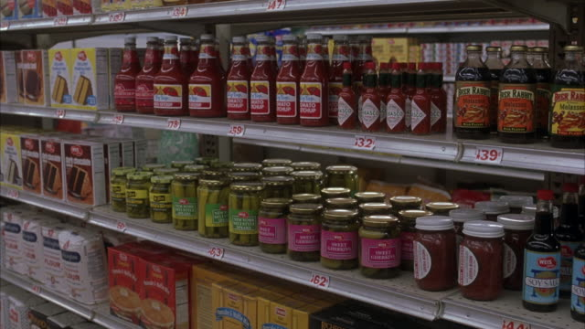 medium angle of grocery store aisle. see condiments shelved. see three shelved tiers of hot sauce, pickled items, and flour. - condiments stock videos and b-roll footage