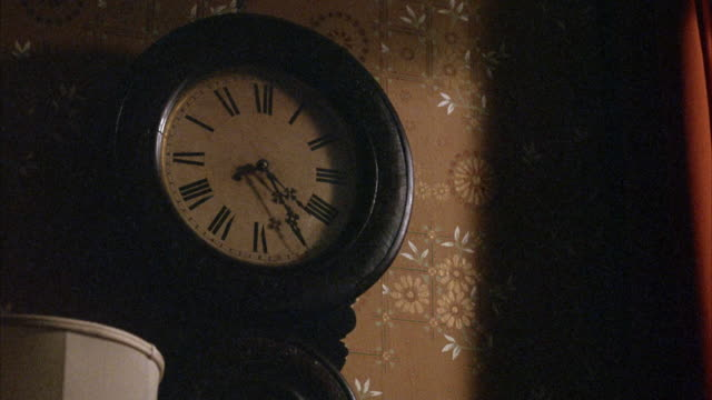 medium angle of dimly lit analog hanging wall clock reading 5:25 am morning. see clock made of dark wood oval frame with metal fancy needles and roman numeral numbering. see tan floral wallpaper on wall and top of white lampshade frame left. - roman numeral stock videos & royalty-free footage