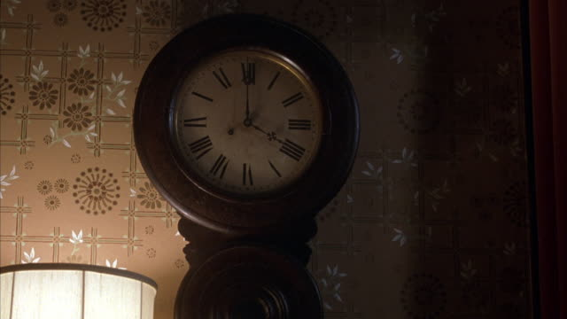 medium angle of dimly lit analog hanging wall clock reading 5:00 am morning. see clock made of dark wood oval frame with metal fancy needles and roman numeral numbering. - roman numeral stock videos & royalty-free footage