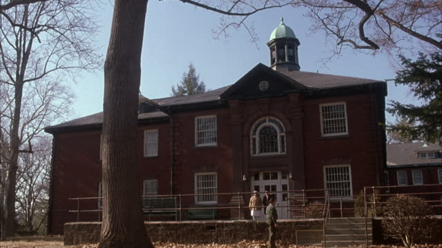 wide angle of 19th century red brick building. white trimmed windows. roof with domed cupola. man rakes leaves in foreground. nurse in white uniform exits building with man in long coat. - https点の映像素材/bロール