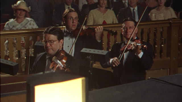 medium angle of musicians playing violins in theater orchestra pit. two musicians stand and leave frame right. see nicely dressed audience laughing and smiling. women wear hats. men wear suits and smoke cigarettes. - musician stock videos & royalty-free footage