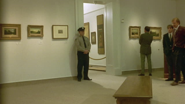 medium angle of art museum. see security guard standing near doorway of exhibit room. see bench in middle of room. see museum patrons walking around. see paintings on wall and sculpture in background. - art gallery stock videos and b-roll footage