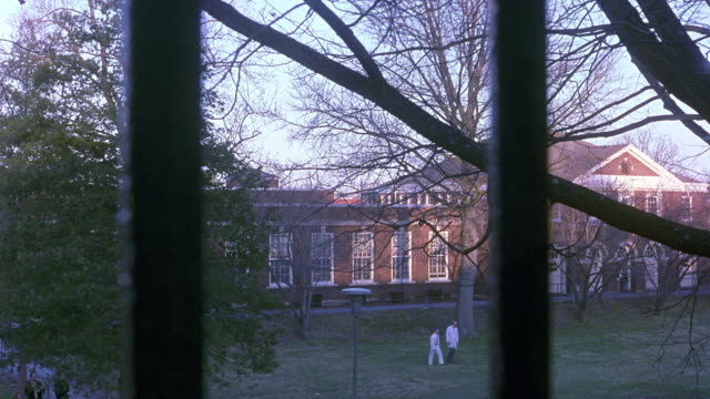 MEDIUM ANGLE OF RED BRICK AND WHITE, MULTI-STORY, COLONIAL BUILDING, COULD BE MENTAL INSTITUTION. SEE PEOPLE ON GRASSY LAWN IN FRONT OF BUILDING. CAMERA THROUGH BLACK WROUGHT IRON GATE.