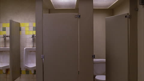 wide angle of stalls and urinals in a men's public restroom. one stall is closed, another is half open and empty. bathroom appears clean. could be rest area, office building, or restaurant. - bathroom stock videos & royalty-free footage