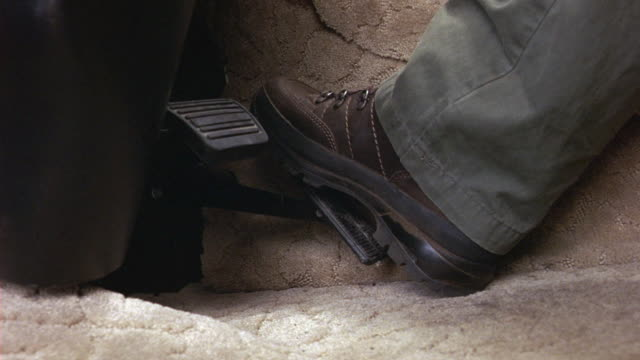 CLOSE ANGLE OF GAS PEDAL AND BRAKE PEDAL IN RV OR TRUCK OR CAR. FOOT WEARING BOOT PRESSES THE PEDALS