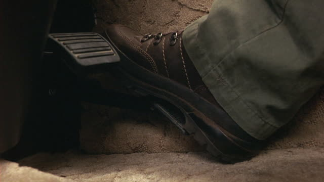 CLOSE ANGLE OF FOOT WITH BOOT PRESSING GAS PEDAL REPEATEDLY.  BRAKE PEDAL ALSO VISIBLE